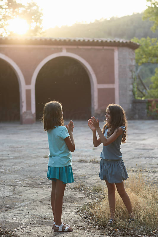 Two young girls playing a hands game at sunset by Miquel Llonch for Stocksy United