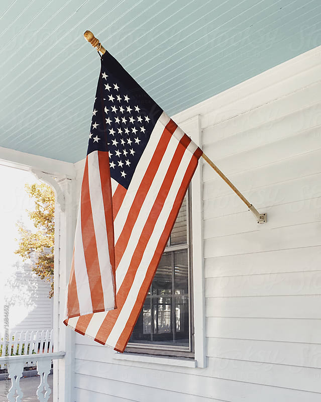 American flag on a white front porch in America