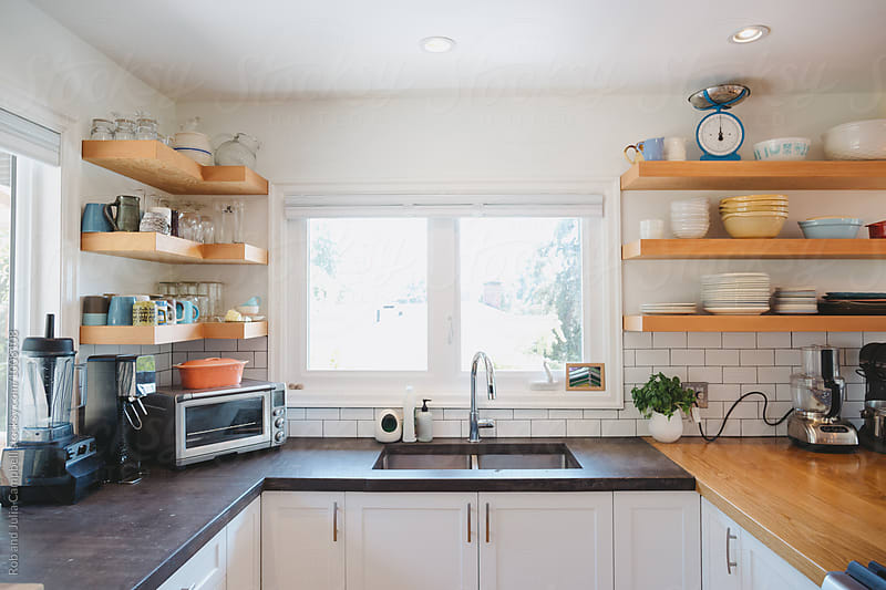 Bright modern kitchen with concrete cement counters and open shelving by Rob and Julia Campbell for Stocksy United