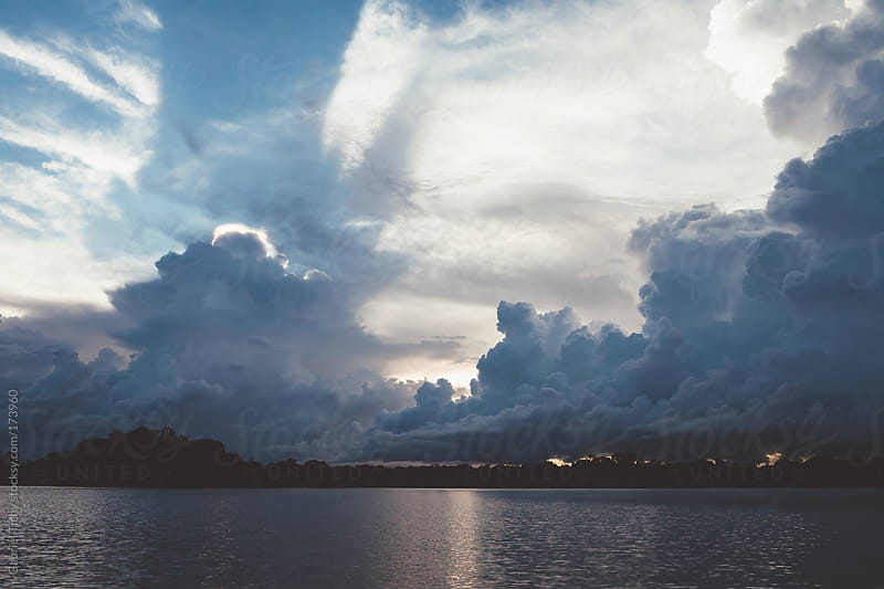 Dramatic cloudscape over a river by Gabriel Tichy for Stocksy United