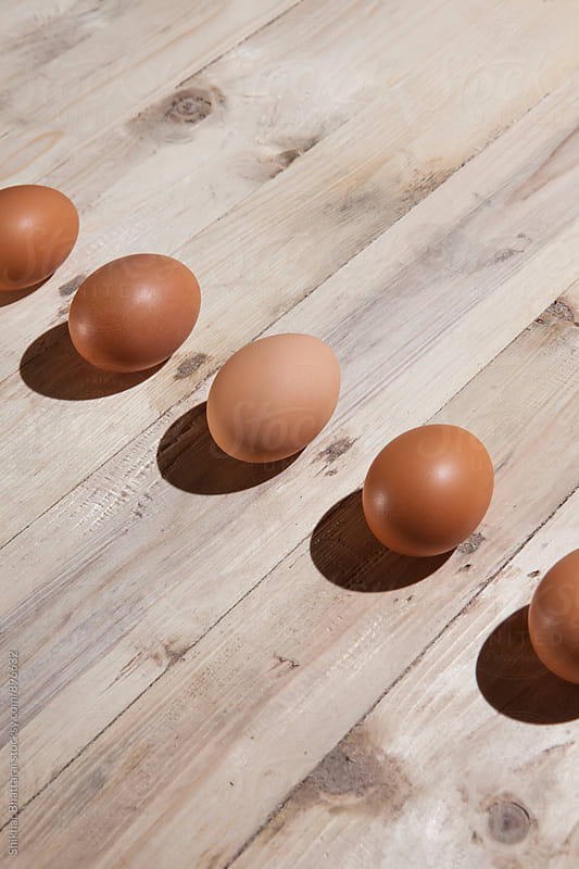 Line of eggs against a wooden background. by Shikhar Bhattarai for Stocksy United