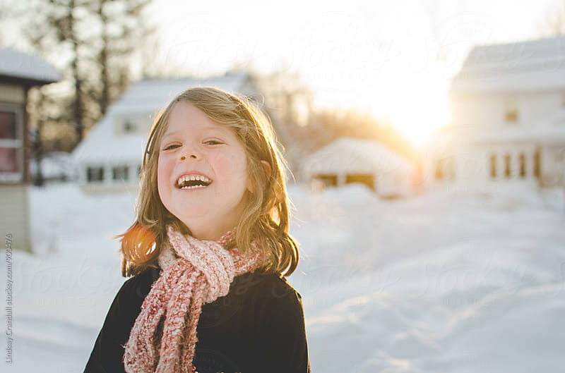 Laughing child outside in winter by Lindsay Crandall for Stocksy United
