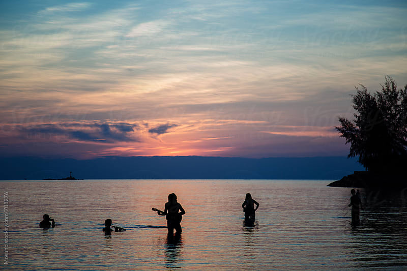 People Playing Instruments in the Shallow Water at Sunset by Mosuno for Stocksy United