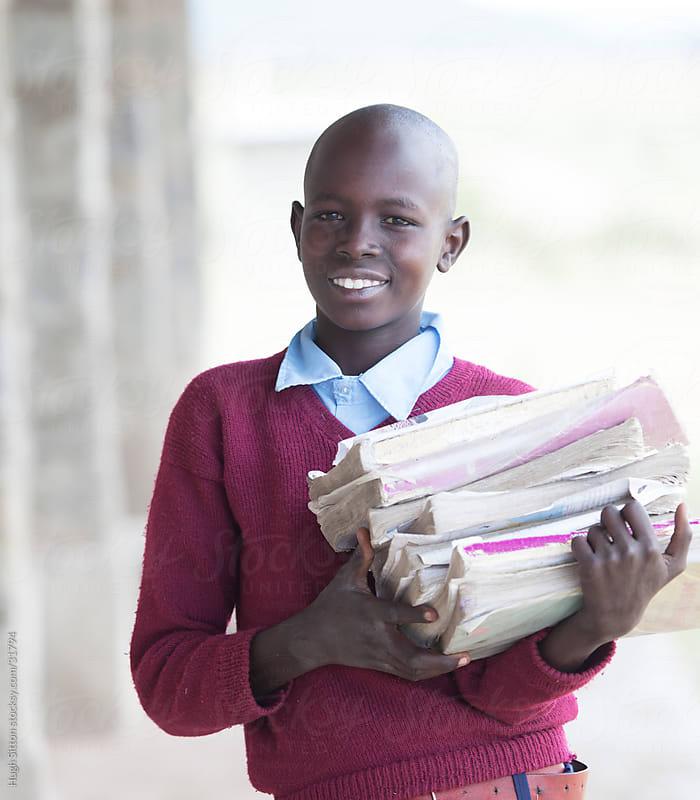Smiling school boy with books. Kenya. by Hugh Sitton for Stocksy United