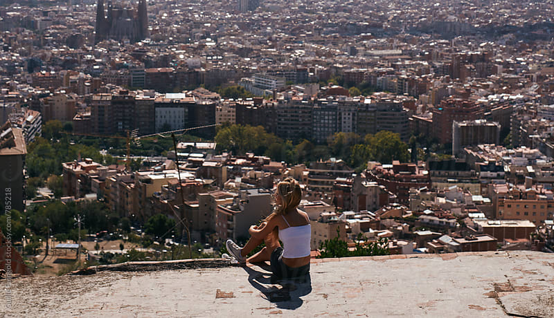 young woman sitting with Barcelona on Background by Guille Faingold for Stocksy United