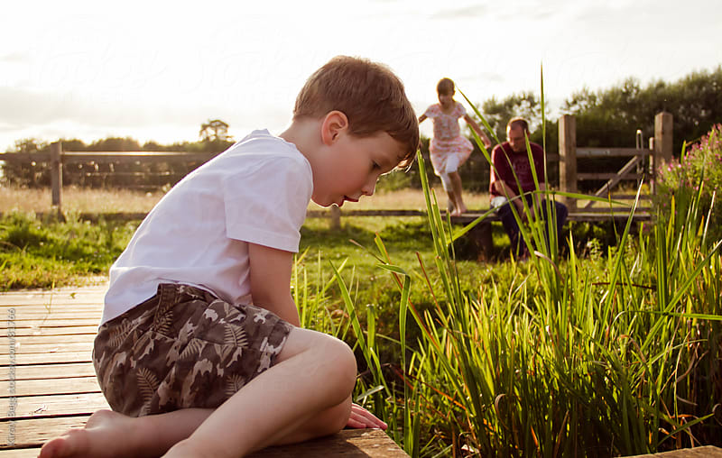 Boy at nature reserve with family (sister and father) by Kirsty Begg for Stocksy United
