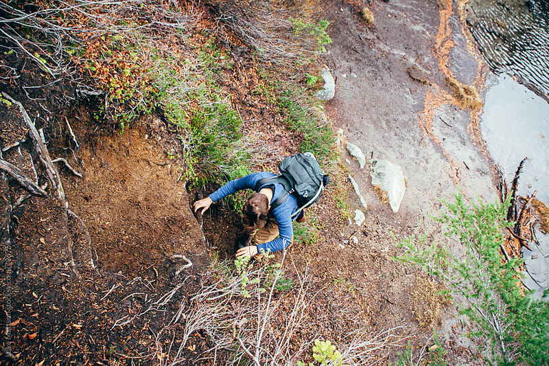 Young Man Climbing Down Dirt Slope Covered In Roots by Luke Mattson for Stocksy United