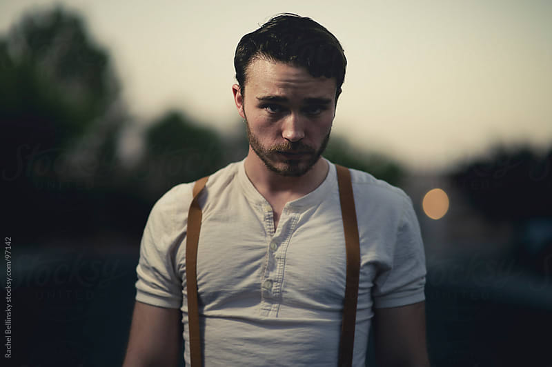 A handsome young man stands outside at twilight by Rachel Bellinsky for Stocksy United