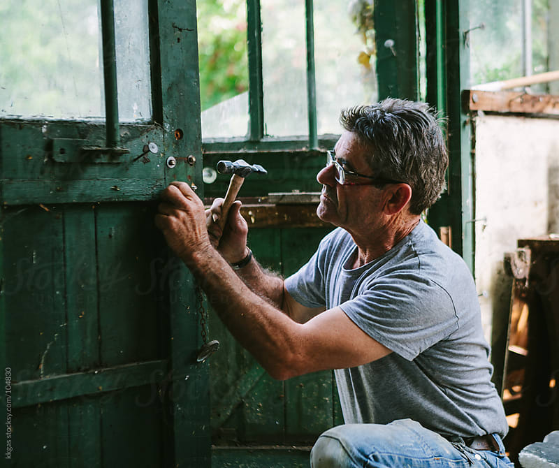 Man working on a wooden door by kkgas for Stocksy United