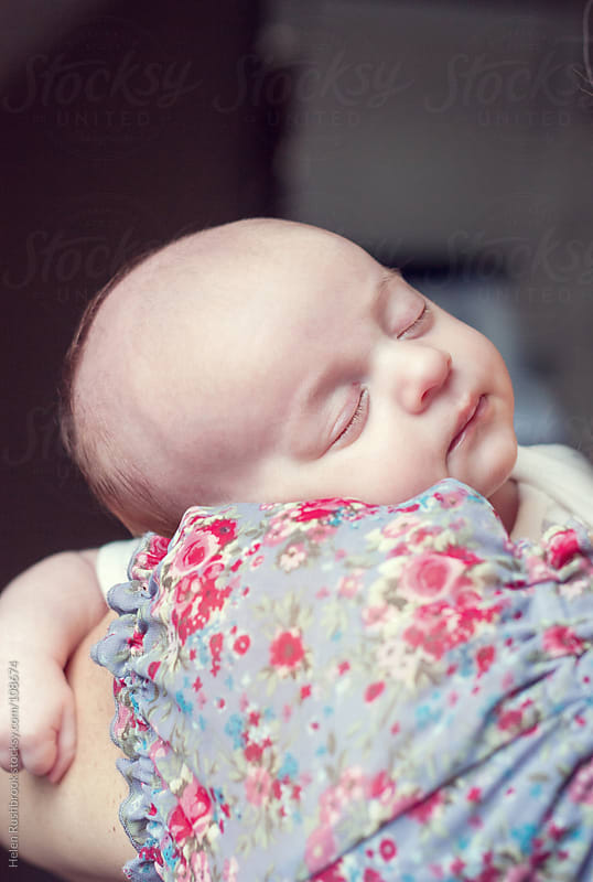 A sleeping baby on his mother's shoulder by Helen Rushbrook for Stocksy United