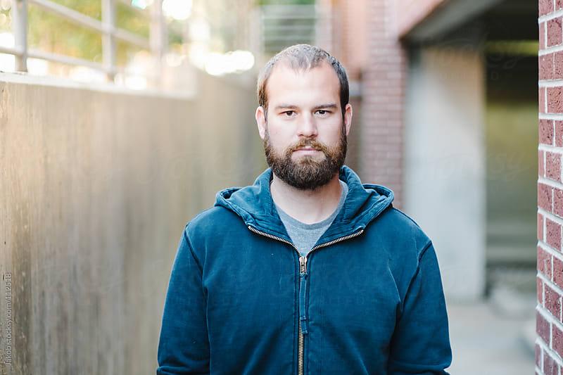 Portrait of a bearded man in a hoodie by Jakob for Stocksy United