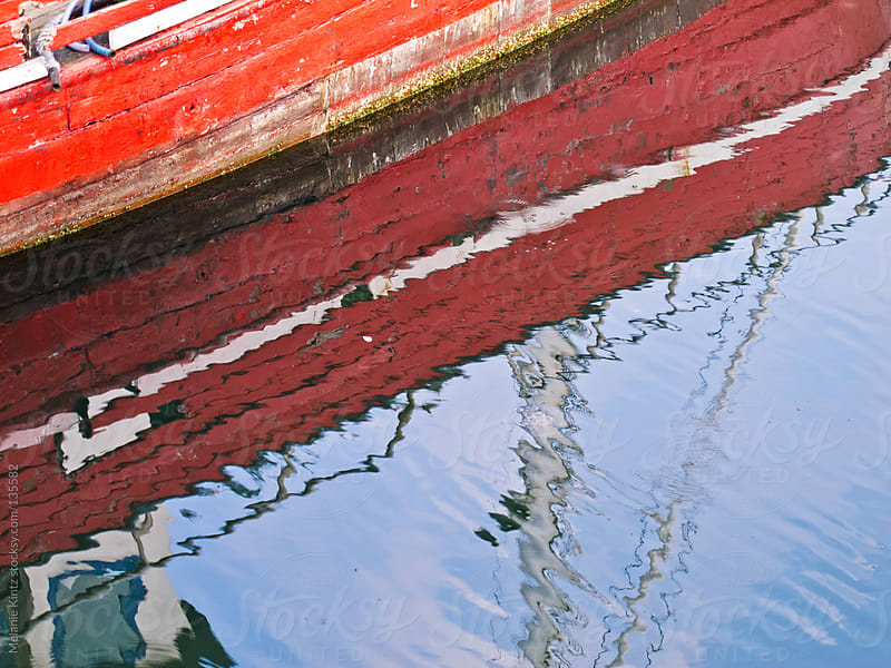 Sides of a red boat reflecting in water by Melanie Kintz for Stocksy United