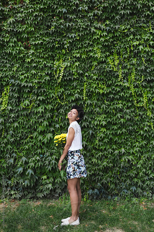 Smilingl girl holding a bouquet of yellow flowers by michela ravasio for Stocksy United