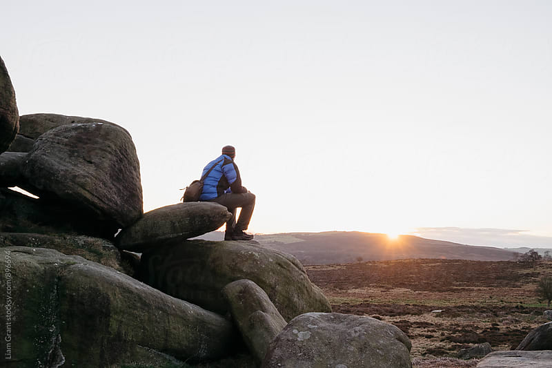 Male sat on rock formations at sunset. Owler Tor, Derbyshire, UK. by Liam Grant for Stocksy United