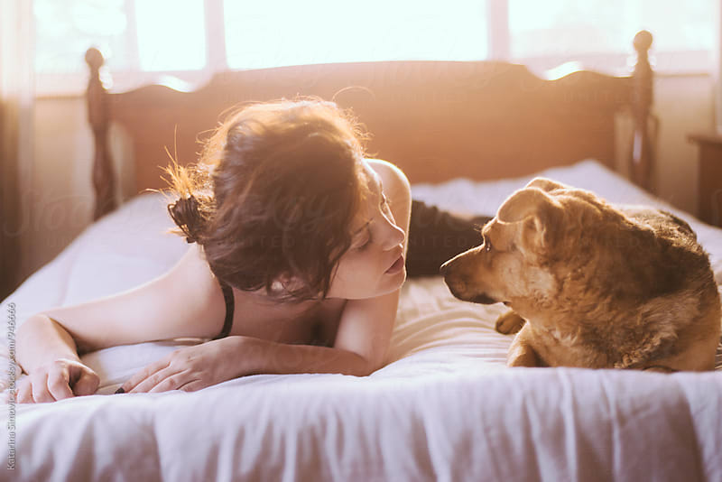 Portrait of beautiful woman with her dog lay in bed by Katarina Simovic for Stocksy United