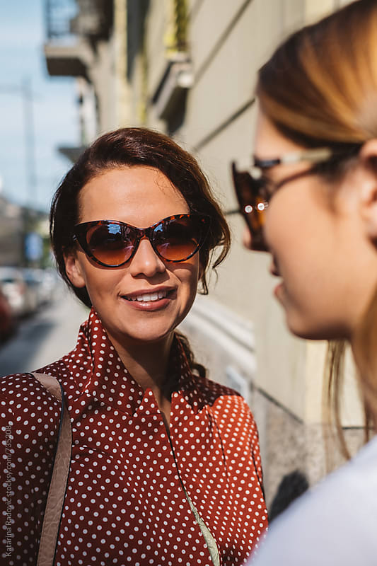 Two Stylish Female Friends Standing on the Street by Katarina Radovic for Stocksy United