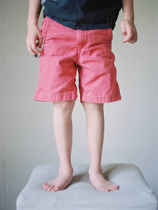 little boy standing on a stool in shorts by Meghan Boyer for Stocksy United