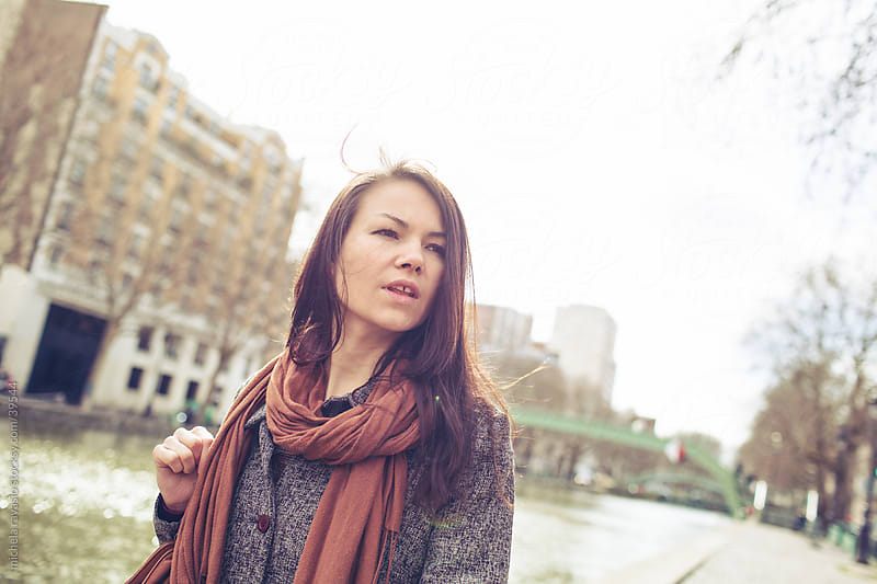 A woman walking along a canal. by michela ravasio for Stocksy United