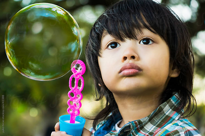 Asian little boy with a large soap bubble by yuko hirao for Stocksy United