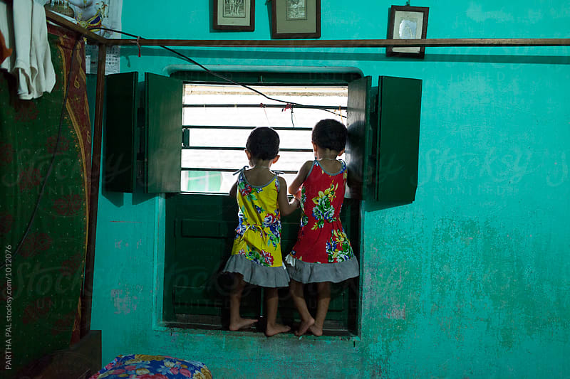 Twin girls looking through wndow by PARTHA PAL for Stocksy United