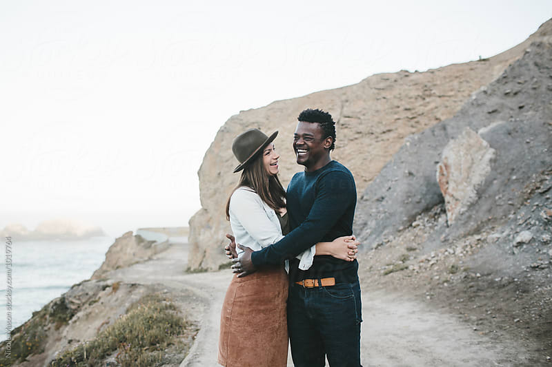 couple laugh together on path in front of rocky landscape by Nicole Mason for Stocksy United
