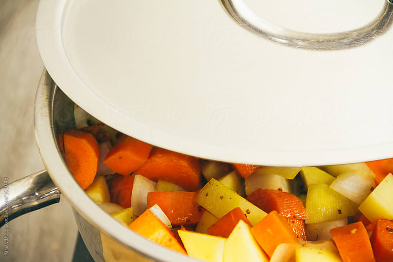 Chopped vegetables cooking in a lidded saucepan by Kirsty Begg for Stocksy United