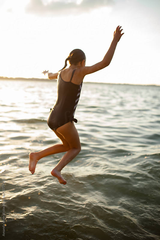 Preteen girl jumping into the lake in the late evening by Amanda Worrall for Stocksy United