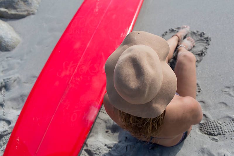 Girl with hat sit on the beach with surfboard by MELCHIOR / PHOTOGRAPHER for Stocksy United