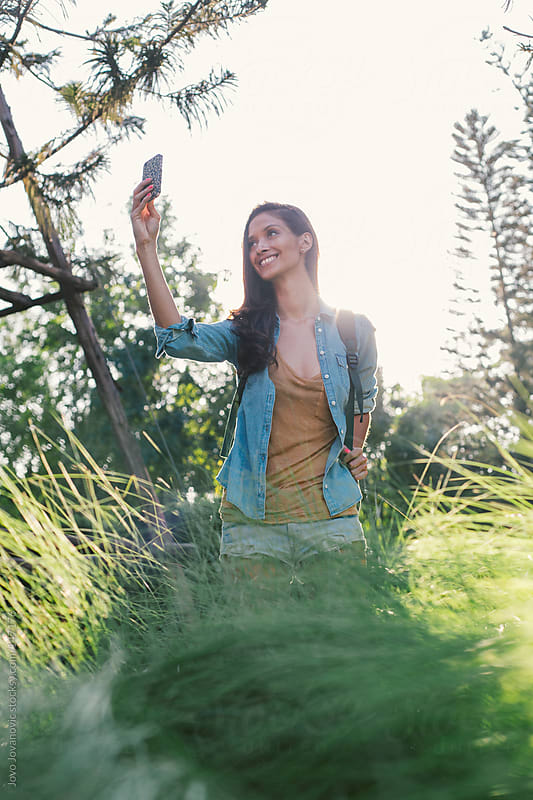 Beautiful girl taking a picture on her phone. by Jovo Jovanovic for Stocksy United