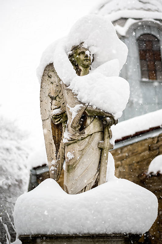 Angel gravestone covered in snow by Pixel Stories for Stocksy United