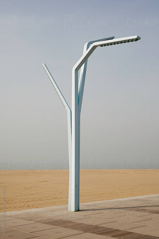 Modern lamppost on the boulevard with the sea and the beach in the background by Ivo de Bruijn for Stocksy United