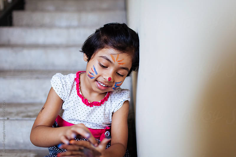 Little girl with a face paint sitting on the stairs by Saptak Ganguly for Stocksy United