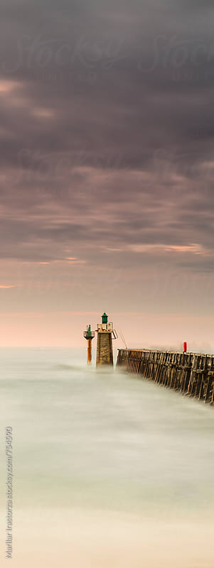 Small lighthouse beside a pier by Marilar Irastorza for Stocksy United