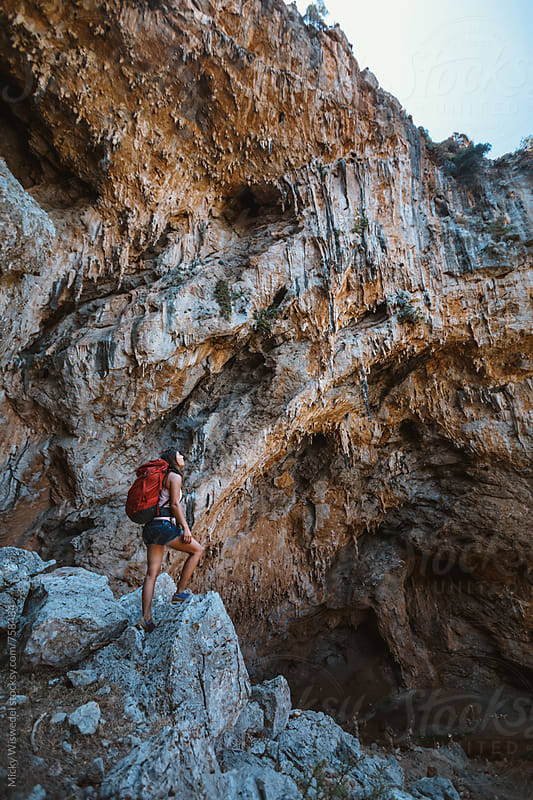 Female hiker exploring a huge limestone cave by Micky Wiswedel for Stocksy United