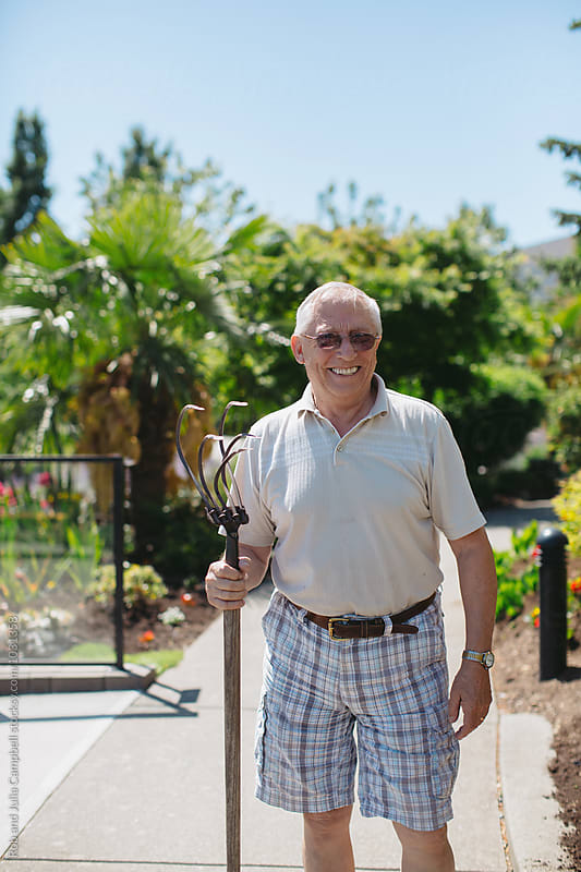 Happy, older caucasian man gardening on sunny day - looking at camera by Rob and Julia Campbell for Stocksy United