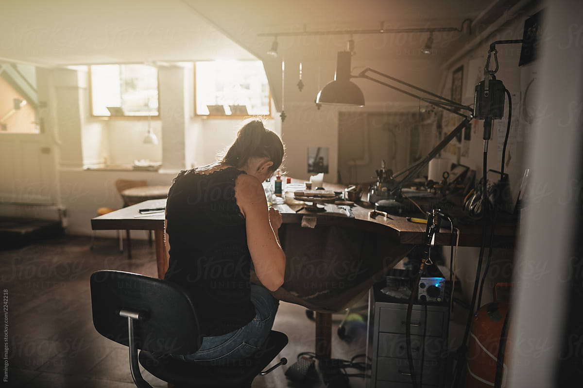 Swell Female Artisan Sitting At A Workbench Making Jewelry By Machost Co Dining Chair Design Ideas Machostcouk