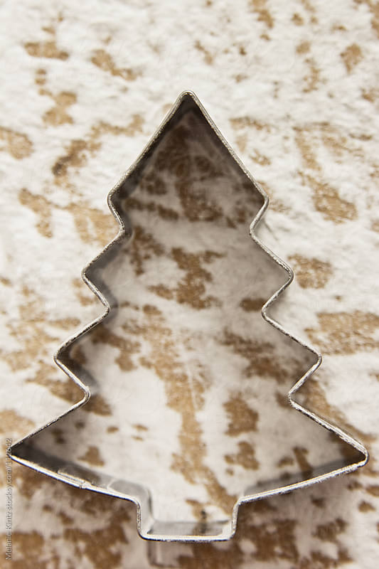 Christmas tree cookie cutter on floured wooden surface by Melanie Kintz for Stocksy United