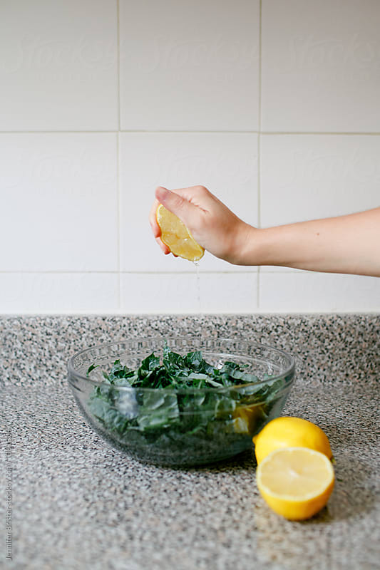 Woman squeezing lemon into kale salad by Jennifer Brister for Stocksy United
