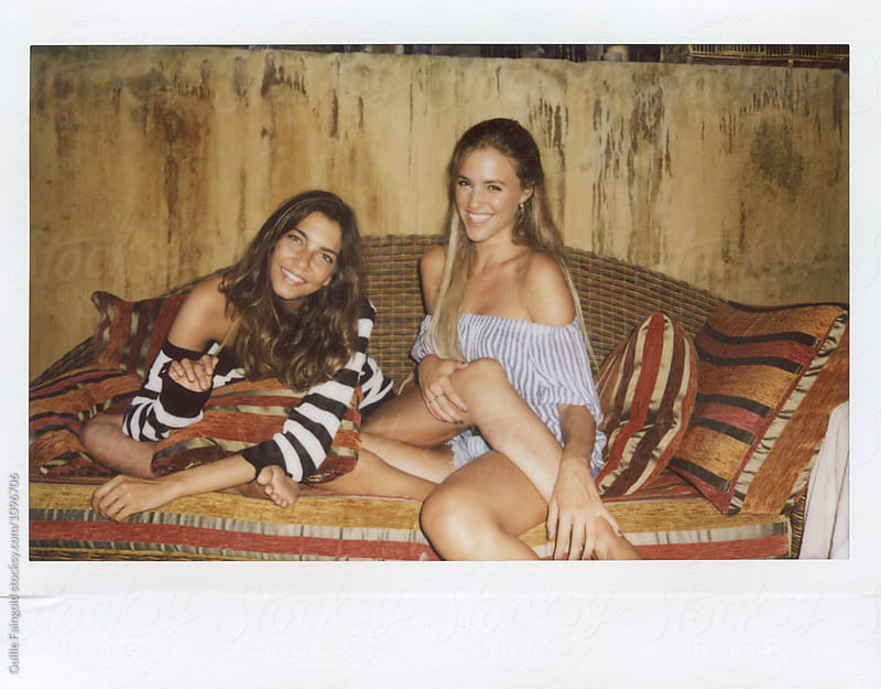 Pretty girlfriends on vintage cozy coach smiling at camera by Guille Faingold for Stocksy United