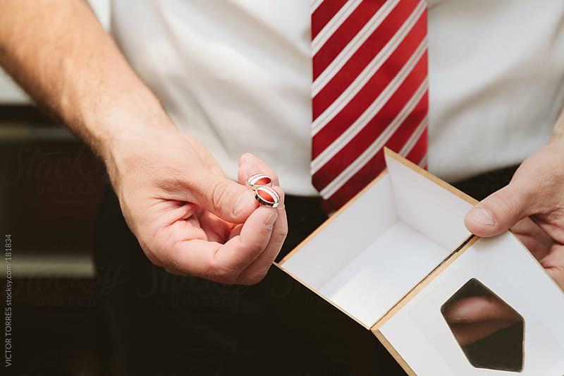 Man Holding a pair of Cufflinks by VICTOR TORRES for Stocksy United
