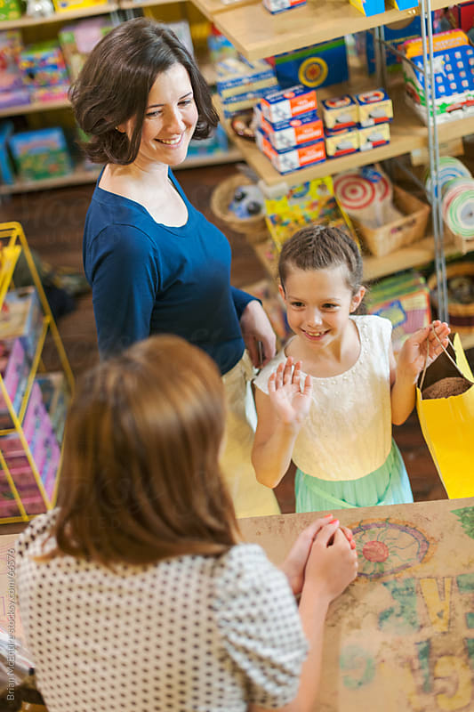 Mother and young daughter shopping in toy store by Brian McEntire for Stocksy United