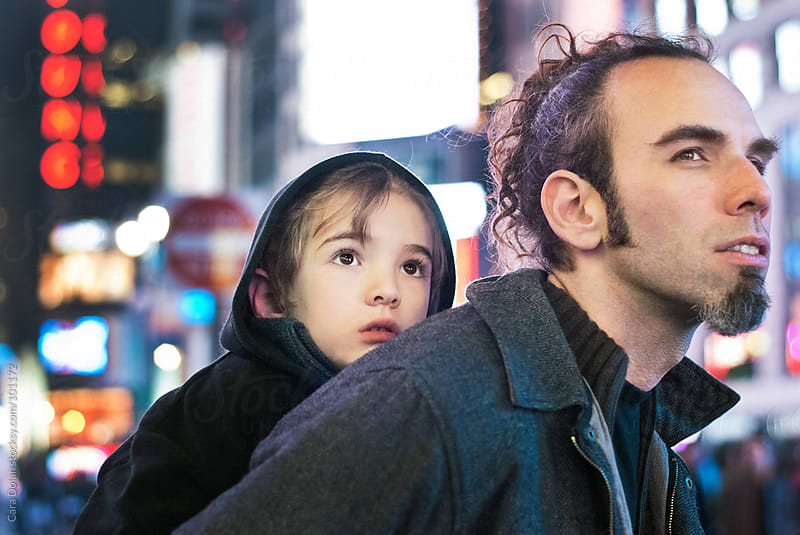 Boy rides on his father's back; sees the lights in Times Square, New York City for the first time by Cara Dolan for Stocksy United