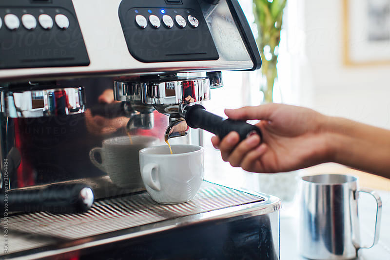 Closeup of young female barista operating coffee maker in cafe. by BONNINSTUDIO for Stocksy United