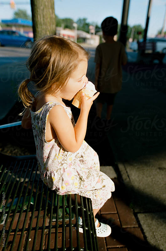 little girl eats ice cream by Maria Manco for Stocksy United