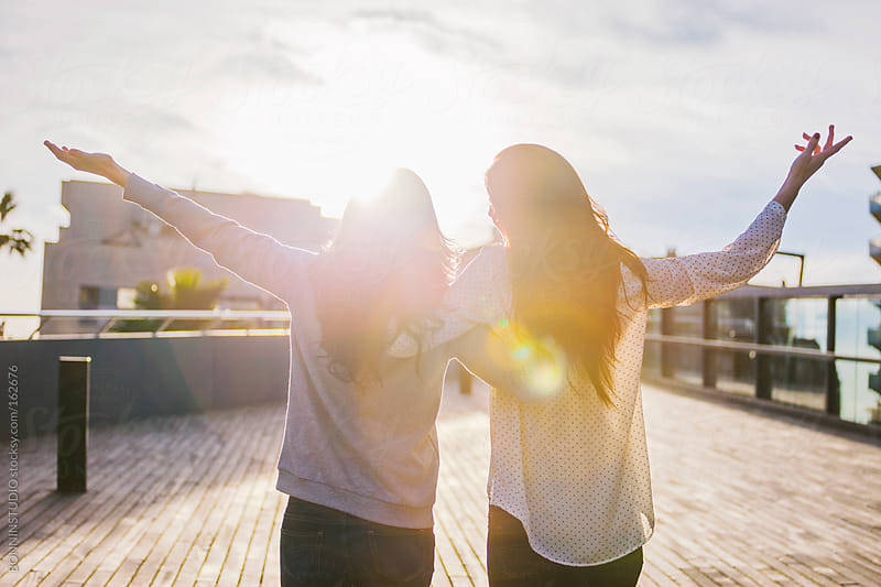 Free happy girlfriends looking a sunset on the city.  by BONNINSTUDIO for Stocksy United
