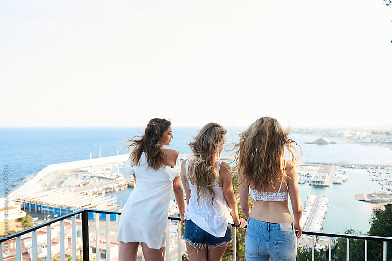 Three girlfriends watching seascape from viewpoint by Guille Faingold for Stocksy United