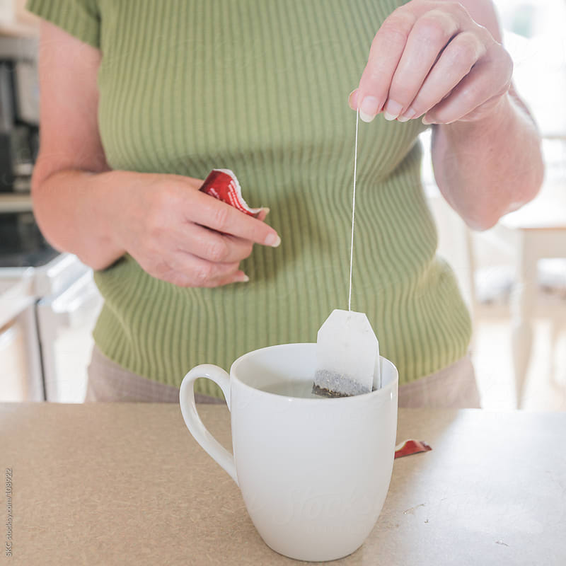 Woman Makes a Fresh Cup of Tea by suzanne clements for Stocksy United