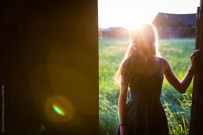 Young girl leaning in doorway of a barn at sunset looking left by Christian Tisdale for Stocksy United