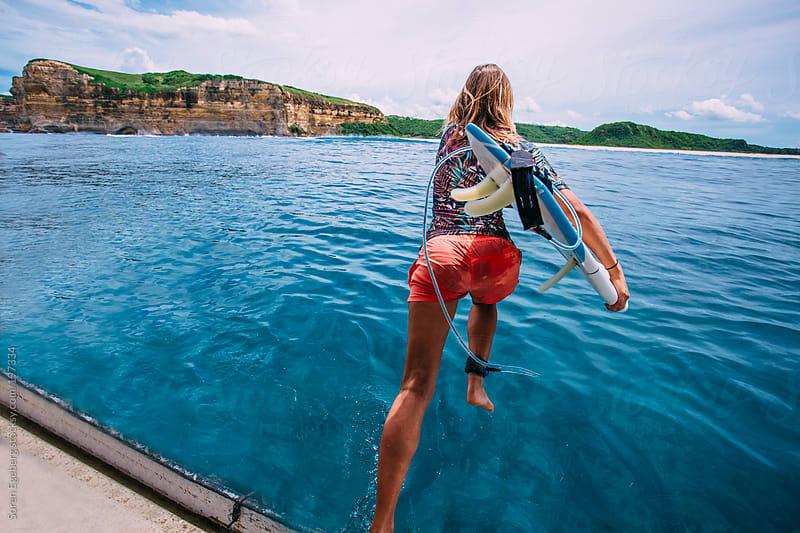 Beautyfull surfer girl jump in  ocean with surfboard by Soren Egeberg for Stocksy United
