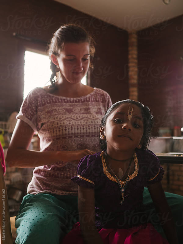 Happy mother combing hair of her adopted indian girl by Martin Matej for Stocksy United